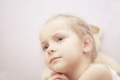 Close up portrait of blond little girl thinking Stock Images