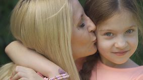 Close-up portrait of blond mother and her little daughter hugging and kissing while sitting in the summer park. Happy stock video
