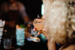 Close up portrait of blonde woman drinking alcoholic cocktail. Close up portrait of a short-haired blonde woman drinking alcoholic cocktail near the bar counter Stock Image