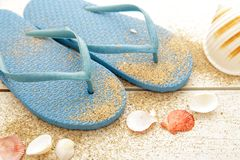 Blue flipflops with sands and seashells. Close up portrait of blue flipflops with sands and seashells on white wooden table Royalty Free Stock Photo