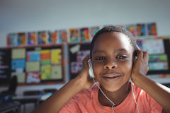 Close up portrait of boy listening music. With headphones in classroom Royalty Free Stock Photos