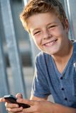 Close up portrait of boy with phone outdoors. Stock Photo