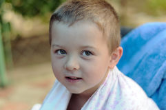 Close-up portrait of a boy wrapped in a towel. After swimming in the garden Royalty Free Stock Photography