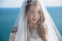 Close up portrait of bride with beautiful make-up, hairstyle and veil on her face with ocean background royalty free stock photos