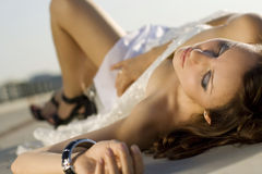 Close-up portrait of bride lying on the road Royalty Free Stock Photo