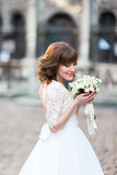 Close-up portrait of the bride smelling the wedding bouquet in the street. Stock Image