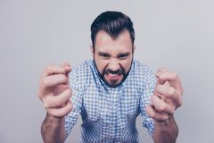 Close up portrait of brunet bearded entrepreneur in smart casual. White and blue checkered shirt, on the pure light blue background, wanting to kill or kick stock photography