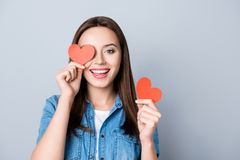Close up portrait of brunette, charming, pretty girl, having two. Small red hearts in  hands, closing one eye with heart symbol,  while standing over grey Royalty Free Stock Photography