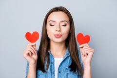 Close up portrait of brunette girl, holding two small red hearts royalty free stock images