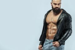 Close-up portrait of a brutal bearded man topless in a leather jacket. Close-up portrait of a brutal bearded man stock image