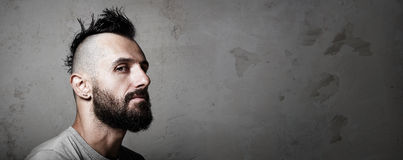 Close-up portrait of a brutal man with mohawk. Portrait of a bearded man with mohawk. Concrete background Stock Photography