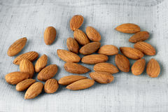 Close up portrait of Burlap sack with almonds spilling out. Close up portrait of Burlap, sack with almonds spilling out Royalty Free Stock Image