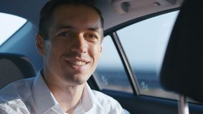 Close-up Portrait of Businessman Traveling in a Car with a Driver. Smiling Young Man in white shirt rides in a Taxi stock footage