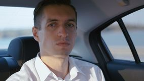 Close-up Portrait of Businessman Traveling in a Car with a Driver. Young Man in white shirt rides in a Taxi stock video
