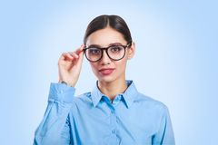 Portrait of a beautiful young business woman standing against blue background royalty free stock images