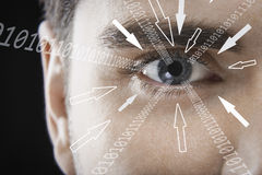 Close-up portrait of businessman with binary digits and arrow signs moving towards his eye against black background royalty free stock image