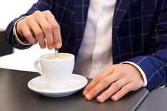 Close up businessman stirring hot coffee at cafe. Close up portrait of businessman stirring hot coffee at cafe Stock Images