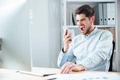 Close-up portrait of businessman in stress talking on phone. Close-up portrait of businessman in stress talking on mobile phone in office Stock Photo