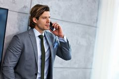 Close up portrait of businessman talking on phone at workplace stock photos