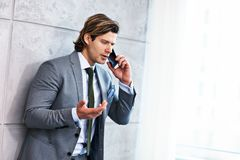 Close up portrait of businessman talking on phone at workplace stock images
