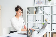 Close-up portrait of a businesswoman at her workplace working with pc, looking in camera, wearing office suit. royalty free stock photos