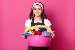 Close up portrait of busy young lady posing with laundry basin, looking directly at camera, being satisfied with quality of stock images
