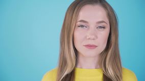 Close-up portrait. Calm girl on a blue background. Isolated background. Place for inscription left 4K stock footage