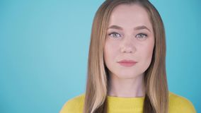 Close-up portrait. Calm girl on a blue background. Isolated background. Place for inscription left. 4K stock video footage