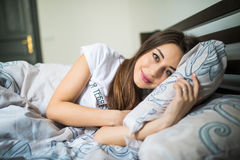 Close up portrait of a calm young pretty woman sleeping and hugging pillow in bed. Portrait of a calm young pretty woman sleeping and hugging pillow in bed Stock Photos