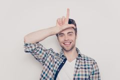 Close up portrait of careless handsome excited cheerful glad fun. Ky funny positive laughing joyful with bristle stubble guy making demonstrating loser sign Stock Photography