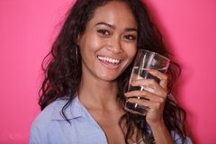 Casual asian woman with a glass of mineral water. Close up portrait of casual asian woman with a glass of mineral water on pink background Royalty Free Stock Image