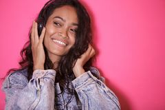 Casual pretty woman enjoy listening a music. Close up portrait of casual pretty woman enjoy listening a music on pink background Royalty Free Stock Photography