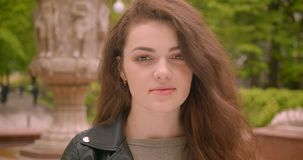 Close-up portrait of caucasian brunette female watches into camera being peaceful in the green city park. Close-up portrait of caucasian brunette female watches stock video