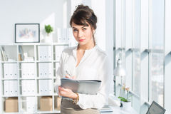 Close-up portrait of a caucasian female office assistant at her workplace. Confident clerk, standing, holding document Royalty Free Stock Images