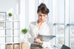 Close-up portrait of a caucasian female office assistant at her workplace. Confident clerk, standing, holding document Stock Photos