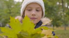Close-up portrait of a Caucasian girl in white hat holding a bunch of yellow leaves and smiling. Pretty young lady. Enjoying autumn day in the park stock video footage