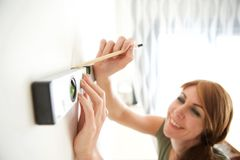 Woman making marks on wall with tools. Close up portrait of caucasian middle aged woman using pencil and spirit level to mark the wall Royalty Free Stock Images