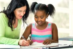 Caucasian teacher helping little african student at desk with sc. Close up portrait of caucasian teacher and little african female student resolving mathematics Stock Images