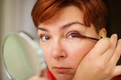 Close up portrait of caucasian Woman putting on brown mascara on eyelashes. She makes light day makeup stock photos