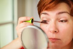 Close up portrait of caucasian Woman putting on brown mascara on eyelashes. She makes light day makeup. royalty free stock image