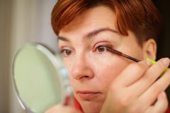 Close up portrait of caucasian Woman putting on brown mascara on eyelashes. She makes light day makeup royalty free stock photography
