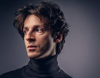 Close-up portrait of a charismatic sensual male in a black sweat. Portrait of a charismatic sensual male in black sweater. Creative personality. Isolated on a Stock Photography
