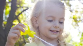 Close-up portrait of a charming blond girl blowing soap bubbles and smiling. Little child with brown eyes playing in the. Park in sunrays stock video