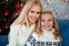 Close-up portrait of charming blonde mother and daughter sitting Stock Images