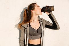 Close-up portrait of charming brunette sport woman drinking wate. R after workout, outdoor Royalty Free Stock Image