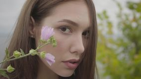 Close-up portrait charming carefree girl looking confident at camera enjoying. Leisure and weekend of a pretty young. Woman outdoors. Real people series stock footage