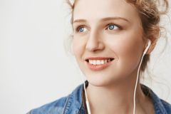 Close-up portrait of charming european ginger girl looking aside with confident and kind expression while listening. Music in earphones and enjoying sunny day Stock Photography