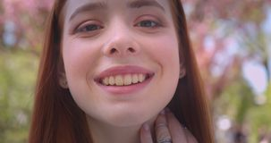 Close-up portrait of charming ginger female model watching dreamily and prettily into camera in pink floral garden. Close-up portrait of charming ginger female stock video