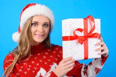 Close up portrait of charming happy cute smiling beautiful girl. Showing and holding in hands a present box, isolated on blue background Stock Photo