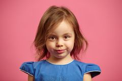 Close up portrait of charming little girl with serious look on pink isolated. royalty free stock images